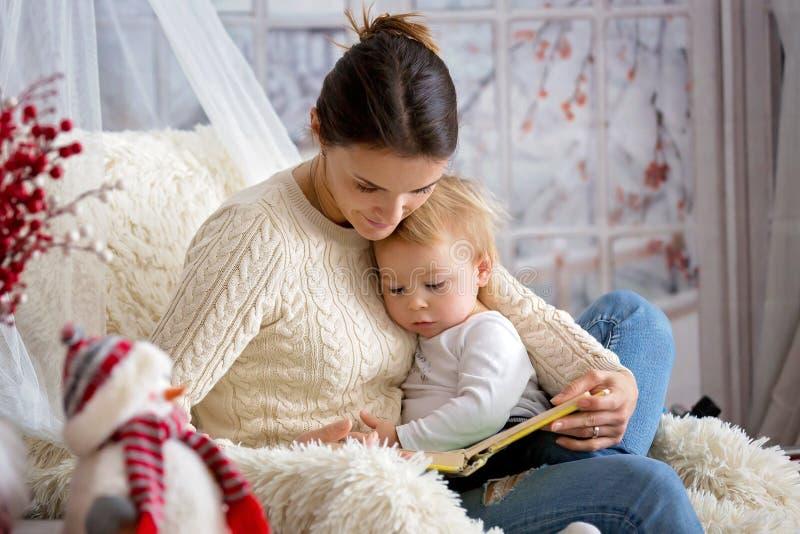 Moeder die haar zitting van de peuterzoon in comfortabele leunstoel de borst geven, wintertijd stock foto