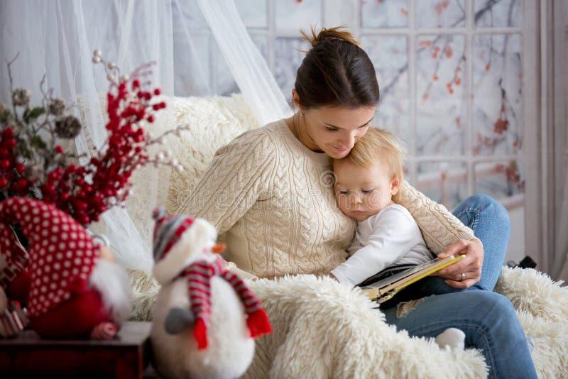 Moeder die haar zitting van de peuterzoon in comfortabele leunstoel de borst geven, wintertijd royalty-vrije stock afbeeldingen