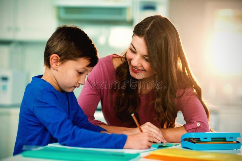 Moeder die haar zoon helpen die thuiswerk doen royalty-vrije stock fotografie