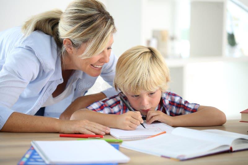 Moeder die haar zoon met thuiswerk helpen stock afbeelding