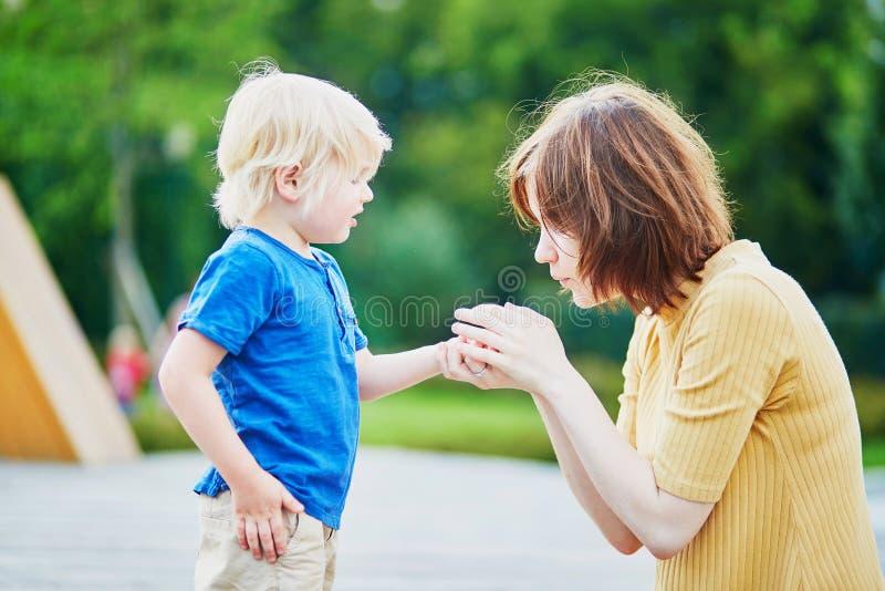 Moeder die haar zoon troosten nadat hij zijn hand verwondde royalty-vrije stock foto