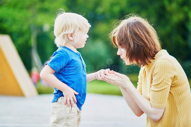 Moeder die haar zoon troosten nadat hij zijn hand verwondde stock foto's