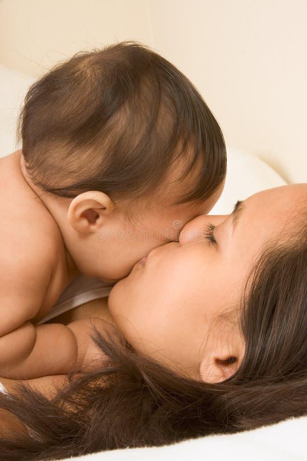Moeder die haar zoon van de babyjongen kust stock foto's