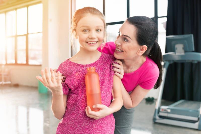 Moeder die het glimlachen van de sportenfles van de dochterholding bekijken met water in gymnastiek royalty-vrije stock foto