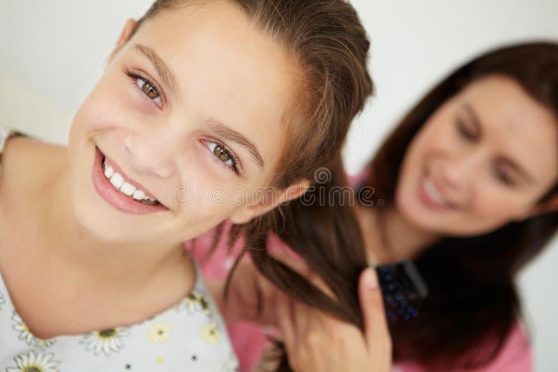 Moeder die het haar van de dochter kamt stock fotografie