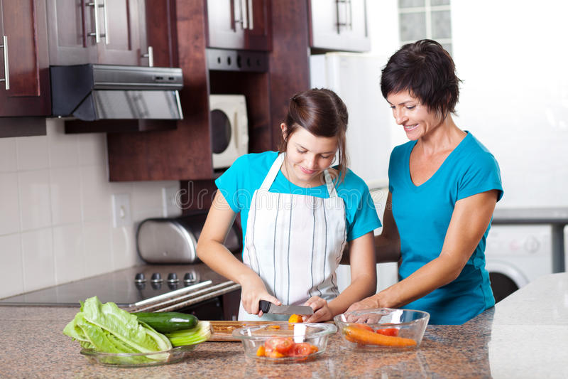 Moeder die het tienerdochter koken onderwijst royalty-vrije stock afbeeldingen