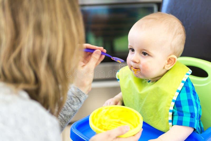 Moeder die hongerige baby in highchair binnen voeden stock afbeeldingen