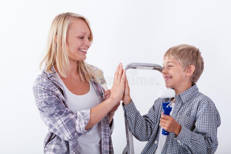 Moeder die hoogte vijf geven aan haar zoon stock foto