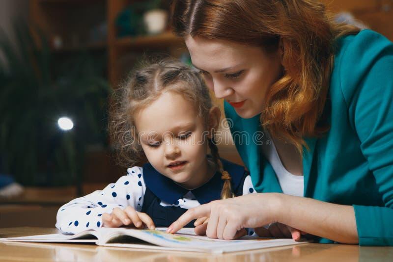 Moeder die jong geitje na school helpen kleuter die thuiswerk met hulp van privé-leraar doen het concept van het huisonderwijs stock fotografie