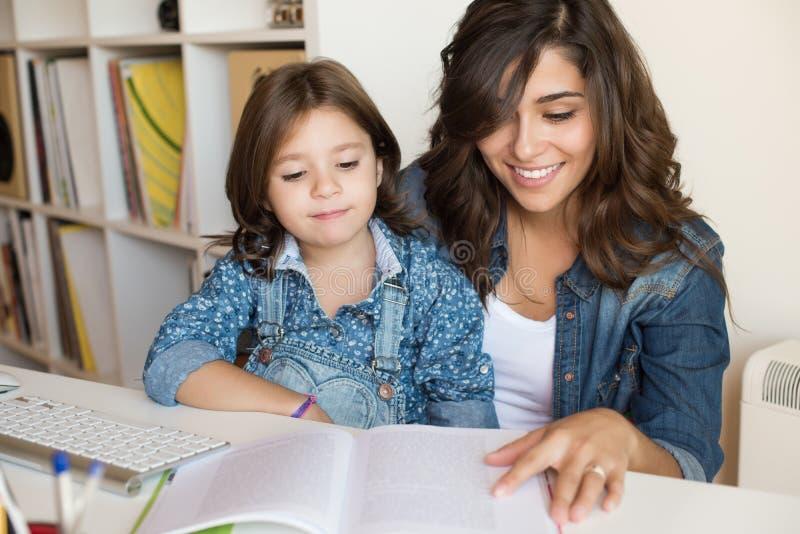 Moeder die kind met thuiswerk helpen stock foto