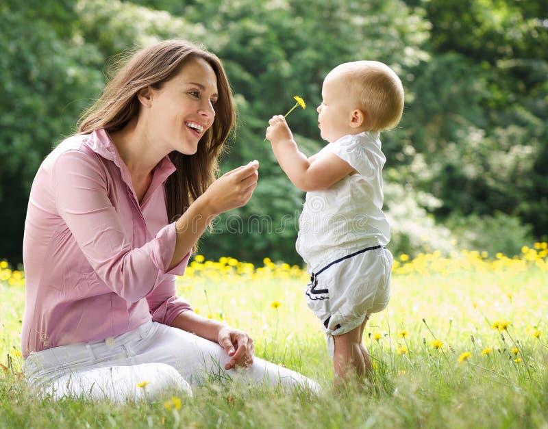 Moeder die kindbloem in het park geven royalty-vrije stock fotografie