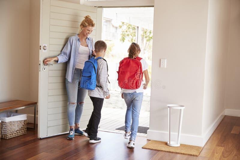 Moeder die Kinderen Klaar krijgen om Huis voor School te verlaten stock afbeelding