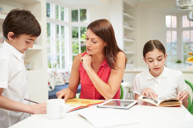 Moeder die Kinderen met Thuiswerk helpen die Tablet gebruiken royalty-vrije stock afbeeldingen