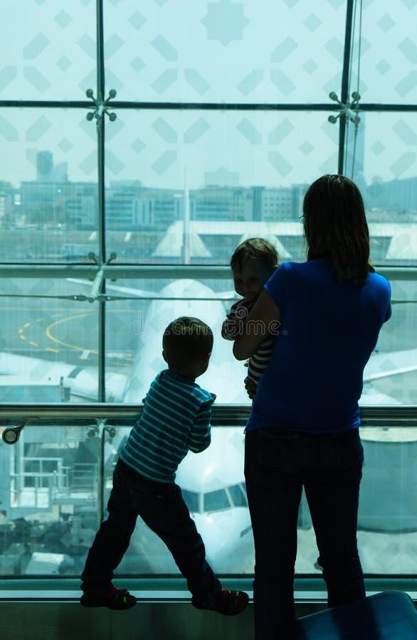 Moeder die met jonge geitjes in de luchthaven wachten royalty-vrije stock afbeelding