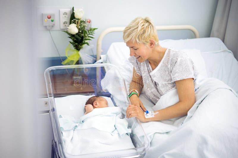 Moeder die met liefde haar pasgeboren babyjongen bekijken royalty-vrije stock foto's