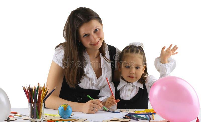 Moeder die met thuiswerk aan haar dochter helpt royalty-vrije stock afbeelding