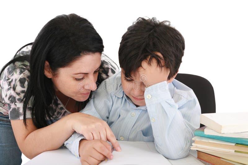 Moeder die met thuiswerk aan haar zoon helpt stock fotografie