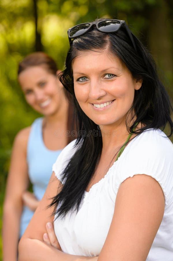 Moeder die met tienerdochter glimlacht op achtergrond royalty-vrije stock foto's