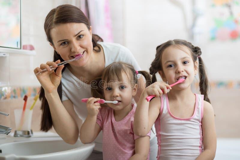 Moeder die met twee jonge geitjestanden in badkamers borstelen stock afbeeldingen