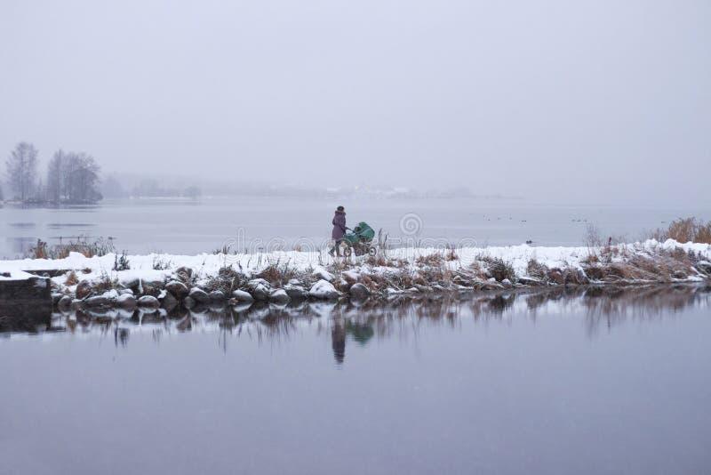 Moeder die met wandelwagen dichtbij meer in de winter lopen stock fotografie