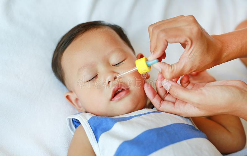 Moeder die neusdalingen voor haar zoon druipen Het concept van de babygezondheidszorg royalty-vrije stock foto's