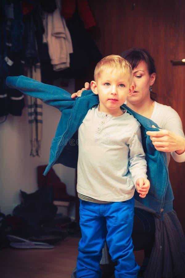 Moeder die omhoog haar zoon in de winterkleren kleden stock foto's