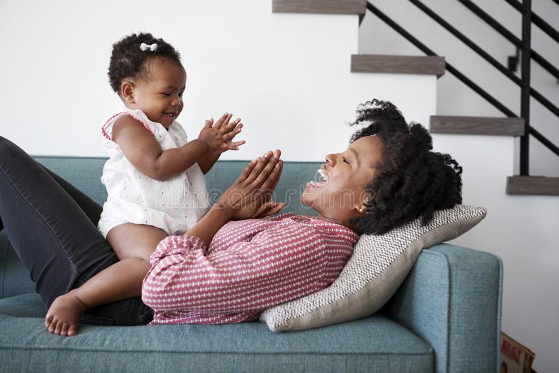 Moeder die op Sofa At Home Playing Clapping-Spel met Babydochter liggen royalty-vrije stock afbeelding