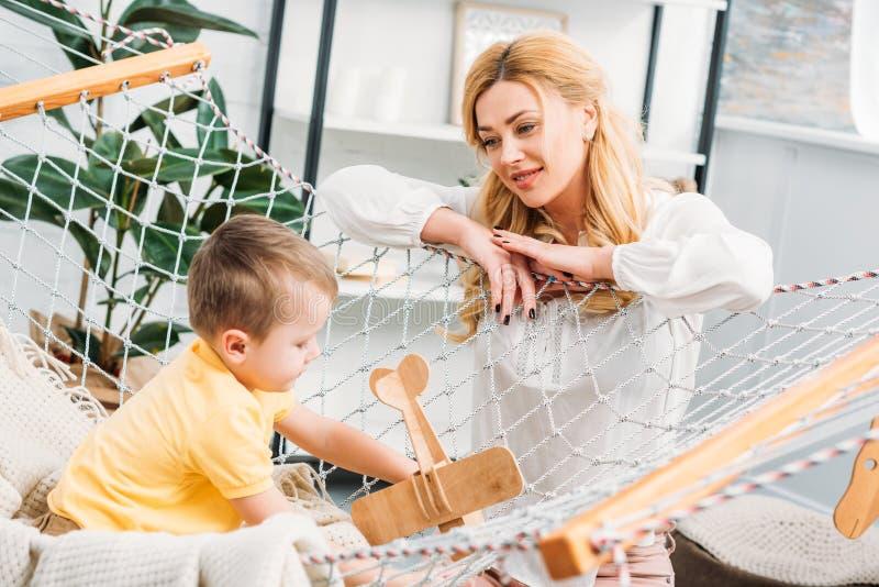 Moeder die op weinig jongen letten speel met houten vliegtuig stock foto's