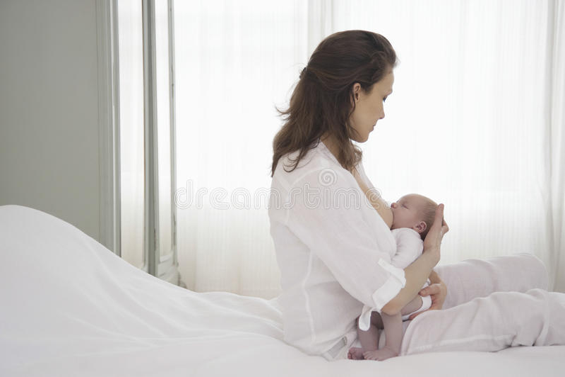 Moeder die Pasgeboren Baby de borst geven royalty-vrije stock afbeeldingen