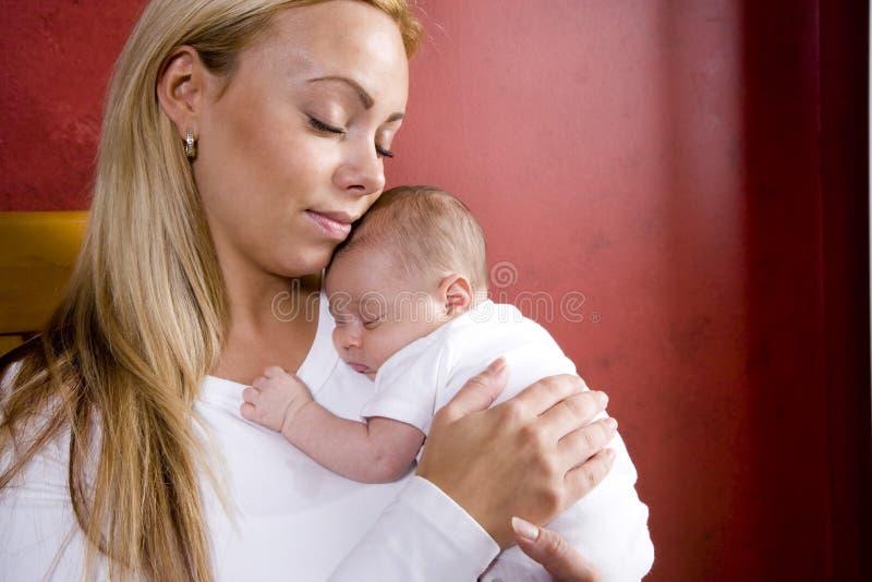 Moeder die pasgeboren baby in schommelstoel houdt stock foto's