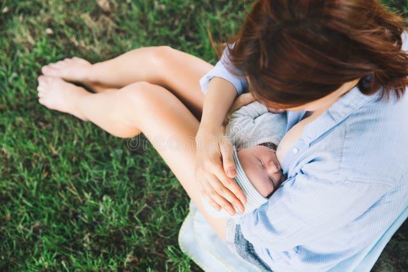 Moeder die pasgeboren babykind op aard de borst geven stock fotografie