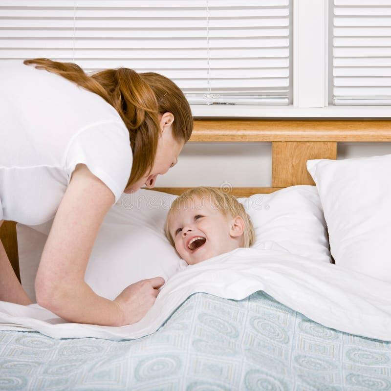 Moeder die praatzieke zoon zet aan bed bij bedtijd royalty-vrije stock afbeeldingen