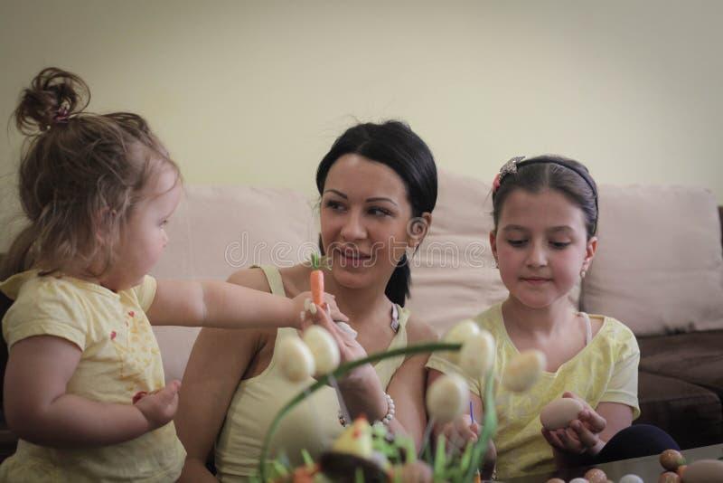 Moeder die pret met jonge geitjes op Pasen hebben royalty-vrije stock afbeelding