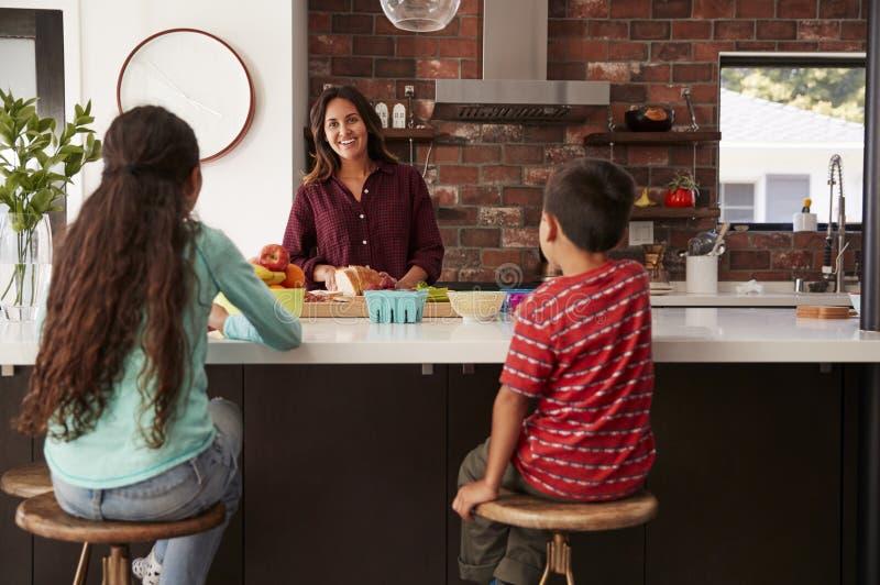 Moeder die Schoolmaaltijden voor Kinderen in Keuken thuis maken stock afbeeldingen
