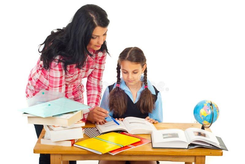 Moeder die schoolmeisje met thuiswerk helpt stock foto's
