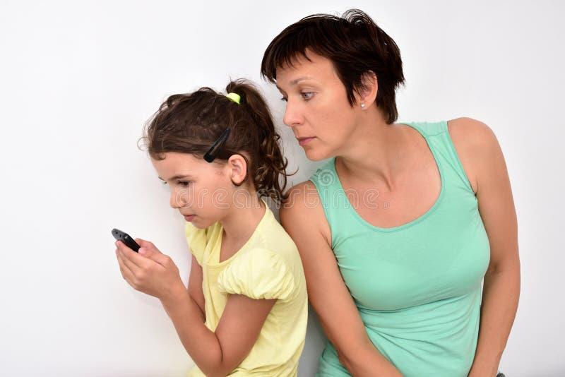 Moeder die smartphone van haar dochter controleren stock foto's