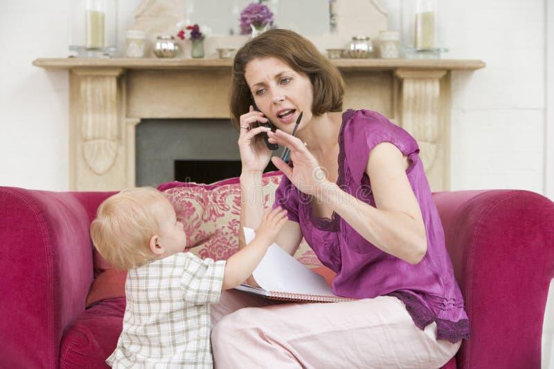 Moeder die telefoon in woonkamer met baby met behulp van royalty-vrije stock foto's