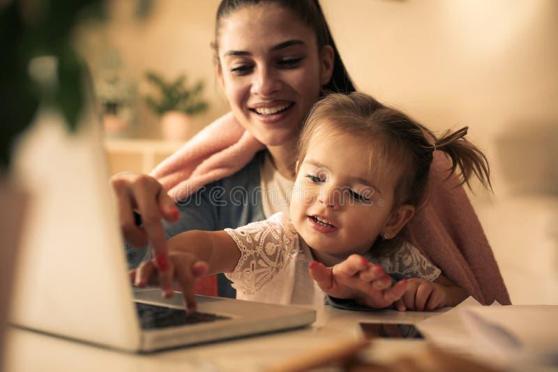 Moeder die thuis dochter onderwijzen aan het gebruiken van laptop royalty-vrije stock afbeelding