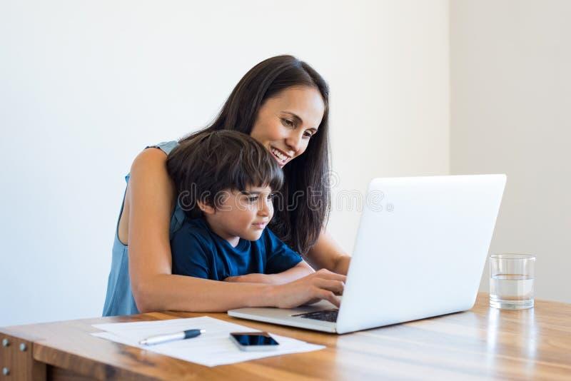 Moeder die thuis met zoon werken stock afbeeldingen