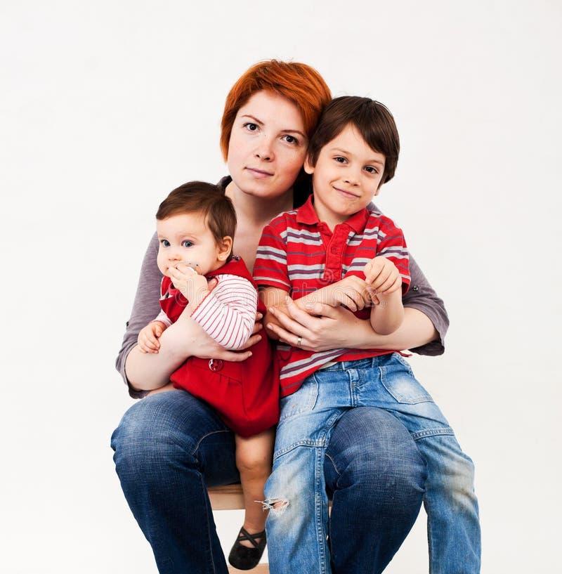 Moeder die twee kinderen houden stock afbeelding
