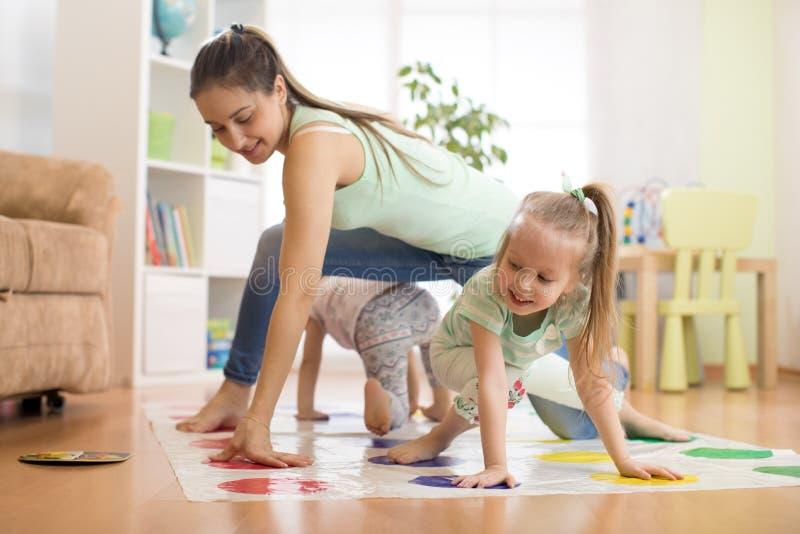 Moeder die twister met haar kinderendochters spelen De gelukkige familie heeft een prettijd in vakantie royalty-vrije stock foto's