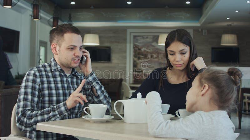 Moeder die vader` s aandacht naar dochter proberen aan te trekken terwijl hij bezig is het spreken om te telefoneren Moeder het i stock afbeeldingen