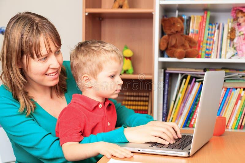 Moeder die van huis met weinig zoon werken royalty-vrije stock afbeelding