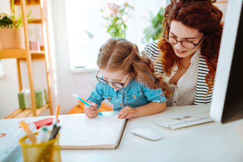 Moeder die ver het bekijken dochter het schilderen werken dichtbij haar royalty-vrije stock foto's