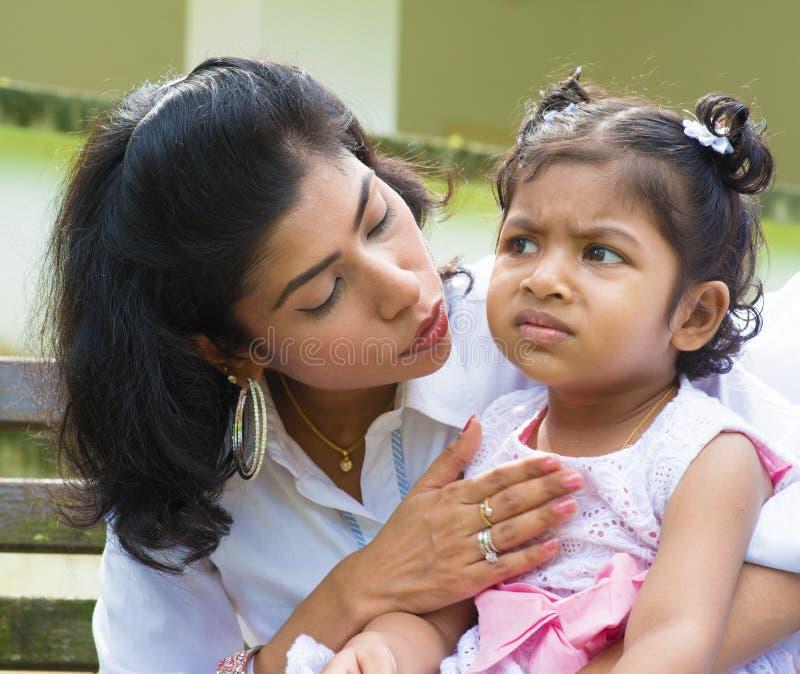 Moeder die verstoord Indisch meisje troosten stock foto