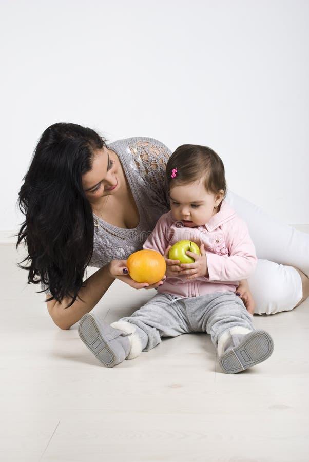 Moeder die vruchten geeft aan haar weinig baby stock afbeeldingen