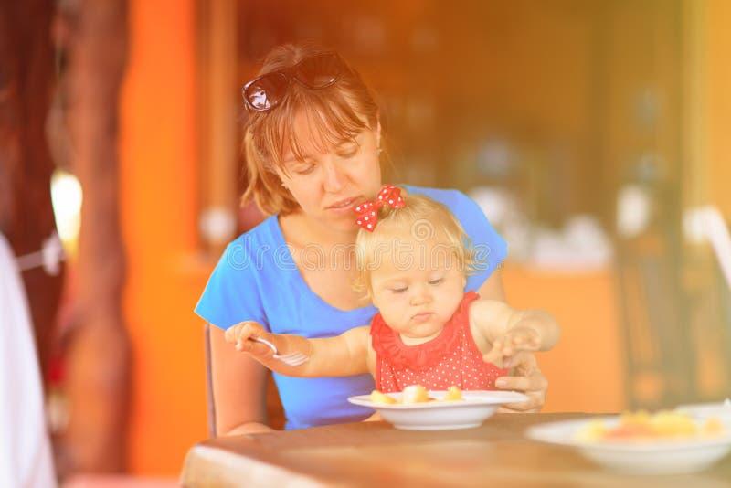 Moeder die weinig dochter in koffie voeden stock foto's