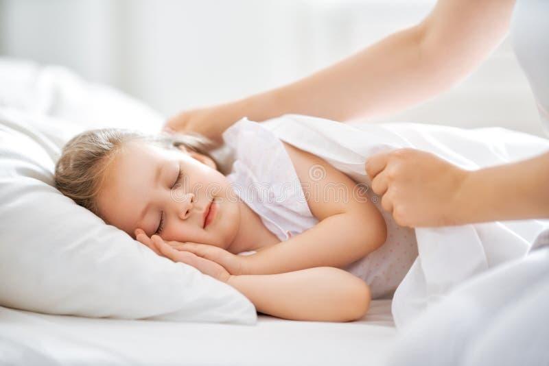 Moeder die weinig slaapmeisje omvatten royalty-vrije stock afbeelding