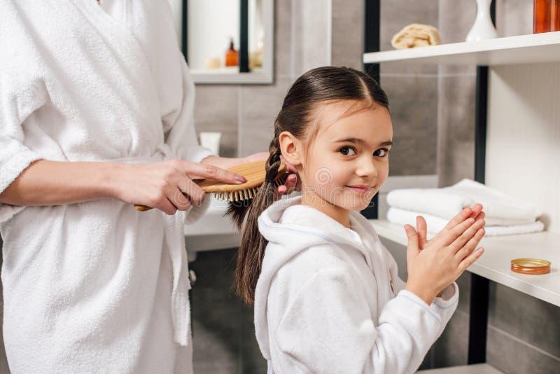 moeder die in witte badjas dochterhaar met houten haarborstel kammen dichtbij planken stock foto's