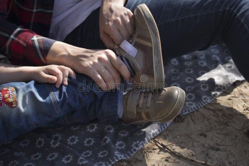 Moeder die zoon helpen om schoenen te dragen Een vrouw vervoert een jong kind stock afbeelding
